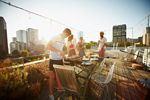 Group of friends on rooftop deck cooking dinner - gettyimageskorea