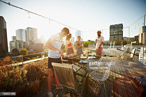 group of friends on rooftop deck cooking dinner - city life stock pictures, royalty-free photos & images