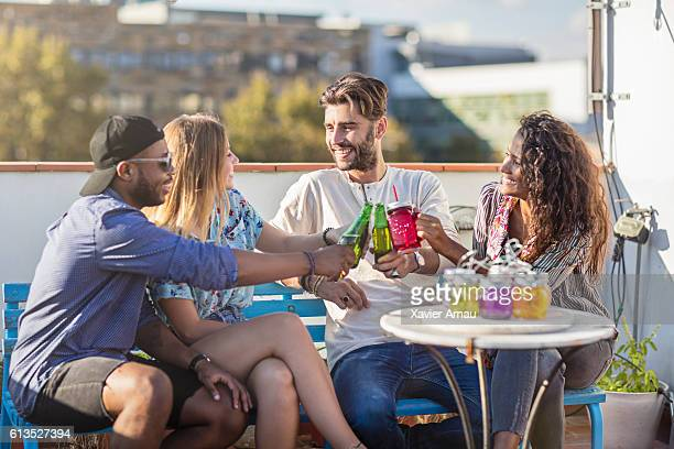 Group of friends on rooftop party having drinks