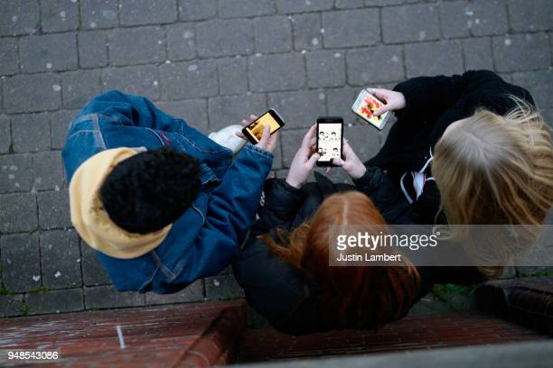group of friends on their mobile phones shot form above in the fading light - adolescence stock pictures, royalty-free photos & images