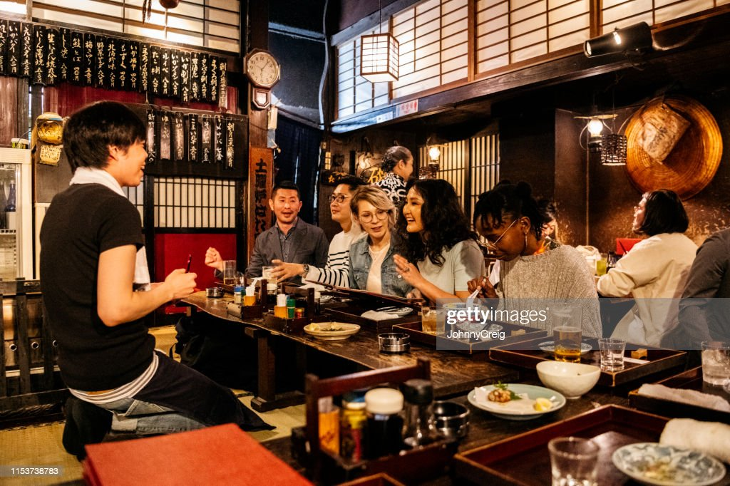 Group of friends ordering food in Japanese Izakaya : Stock Photo