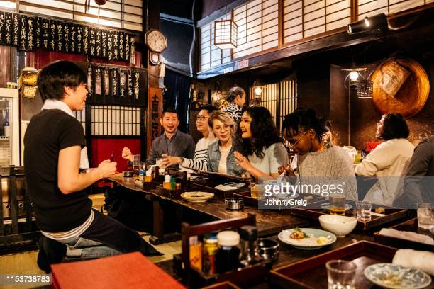 group of friends ordering food in japanese izakaya - tourist stock pictures, royalty-free photos & images