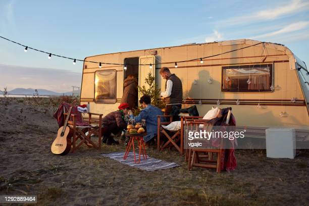 group of friends organizing new year's party in front of their camper trailer - car decoration stock pictures, royalty-free photos & images