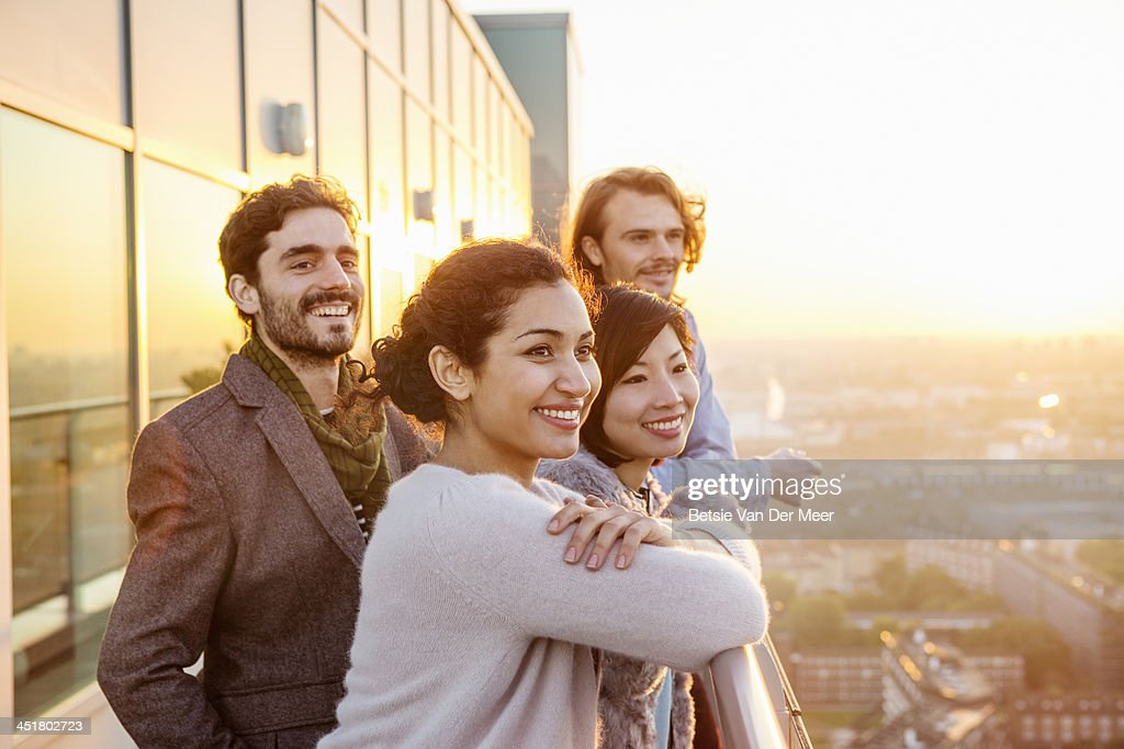 Group of friends overlooking city at sunset. : Stock Photo