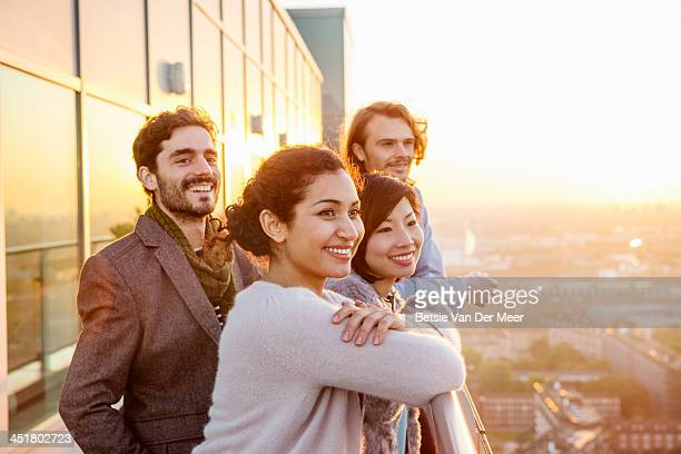 group of friends overlooking city at sunset. - four people stock pictures, royalty-free photos & images