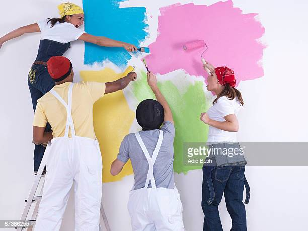 Group of friends painting wall.