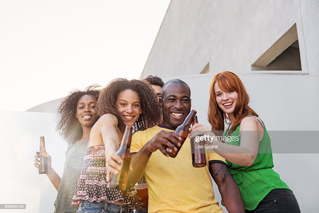 Group of friends partying on balcony : Stock Photo