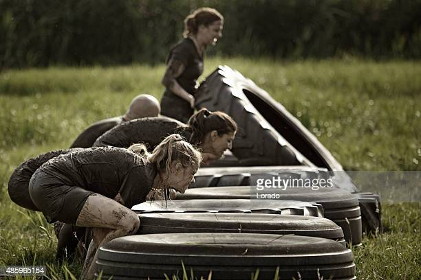 group of friends picking up tyres during mud run