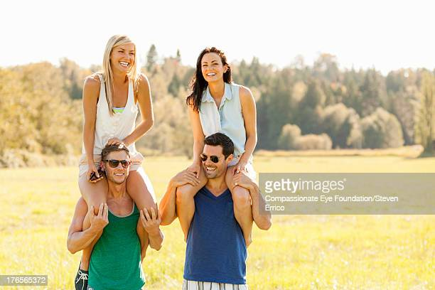 group of friends piggybacking in field - carrying a person on shoulders stock photos and pictures