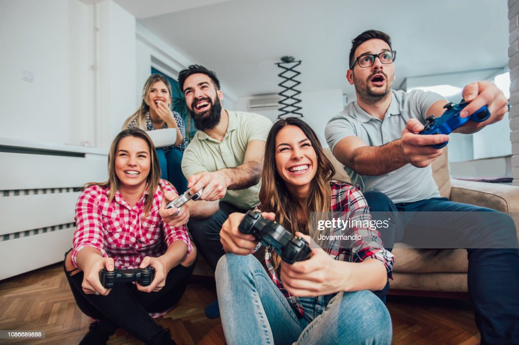 Group of friends play video games together. : Stock Photo