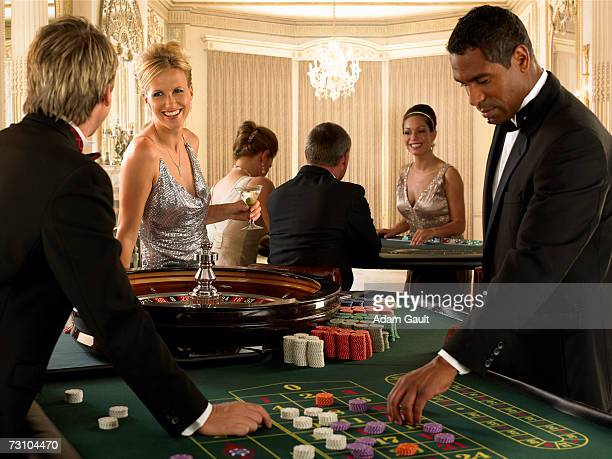Group of friends playing at roulette table in casino