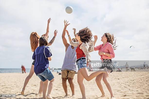 grupo de amigos a jogar na praia - homem pegando mulher imagens e fotografias de stock