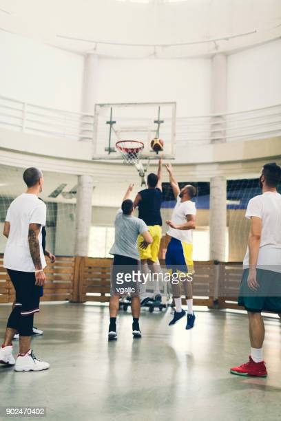 group of friends playing basketball in a school gym - shooting baskets stock photos and pictures