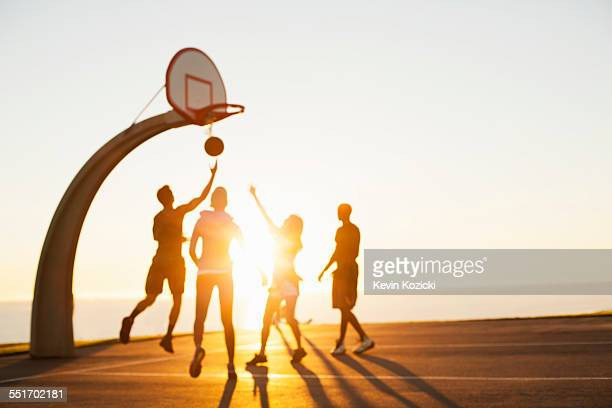 group of friends playing basketball, outdoors - dribbling sports stock pictures, royalty-free photos & images