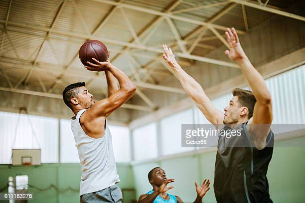group of friends playing basketball - shooting baskets stock photos and pictures