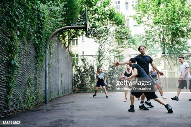 Group Of Friends Playing Basketball Together In The City