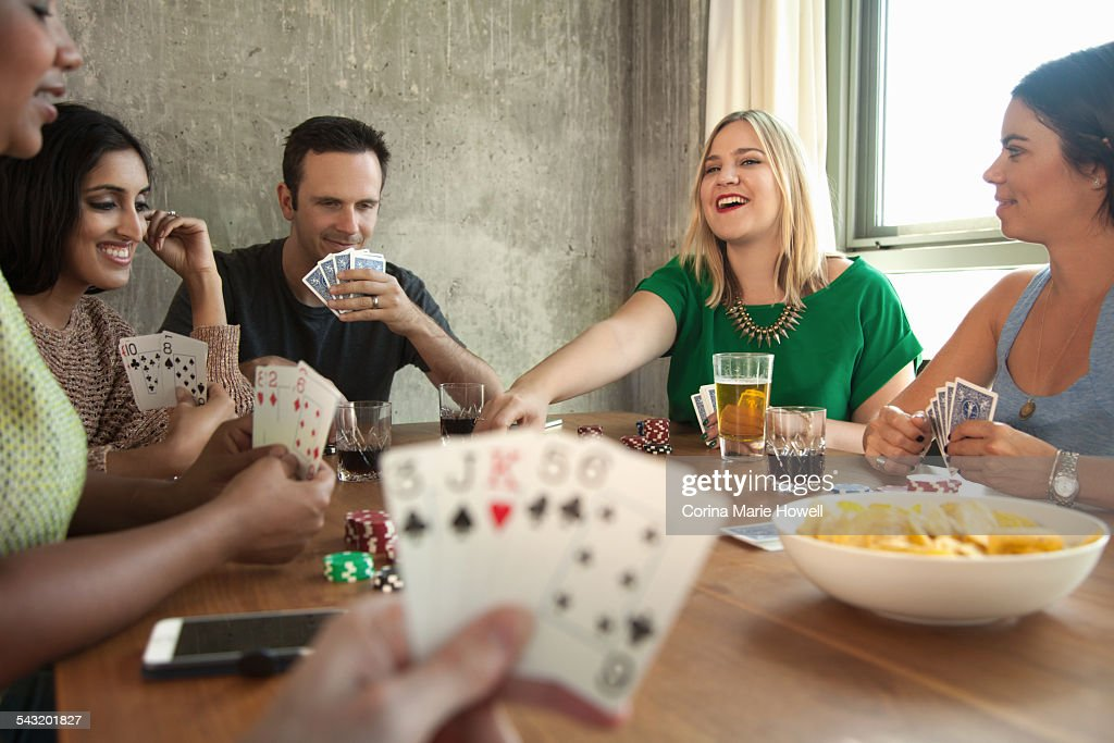 Group of friends playing cards around table : Stock Photo