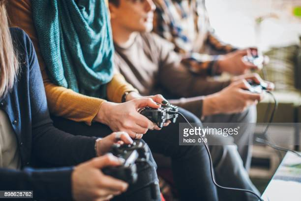 group of friends playing digital games at home. - match sportivo foto e immagini stock