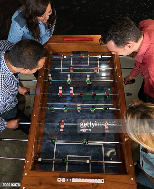 Group of friends playing foosball at a bar