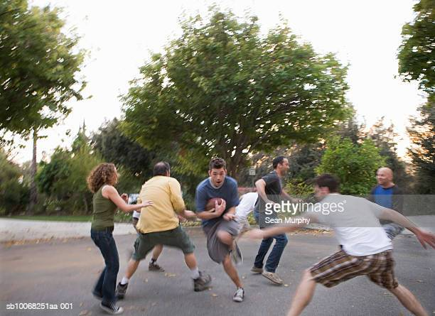 Group of friends playing football in street