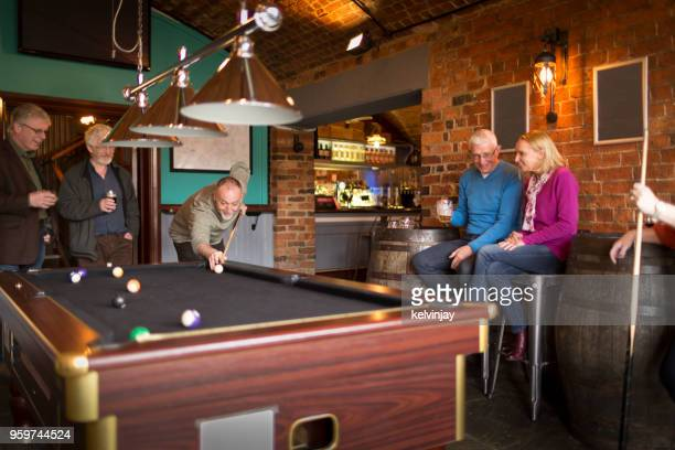 A group of friends playing pool in a bar
