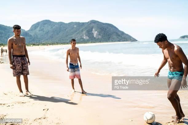 ビーチでサッカーをしている友人のグループ - バーラ地区 ストックフォトと画像