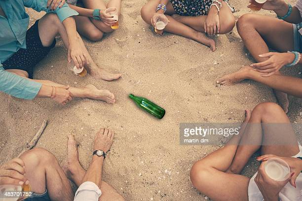 Group of friends playing spin the bottle at the beach