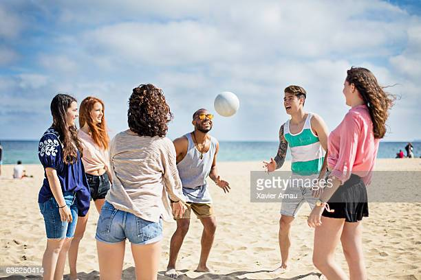 Group of friends playing volley ball on the beach