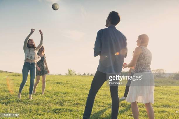Eine Gruppe von Freunden Volleyball zu spielen, im Sonnenuntergang