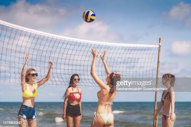 group of friends playing volleyball on beach. - beach volley photos et images de collection