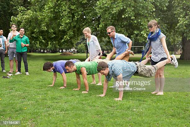 A group of friends playing wheel barrow race