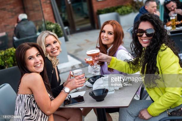 Group of friends pose for a photograph in the beer garden at Dukes 92 bar on April 12, 2021 in Manchester, England. England has taken a significant...