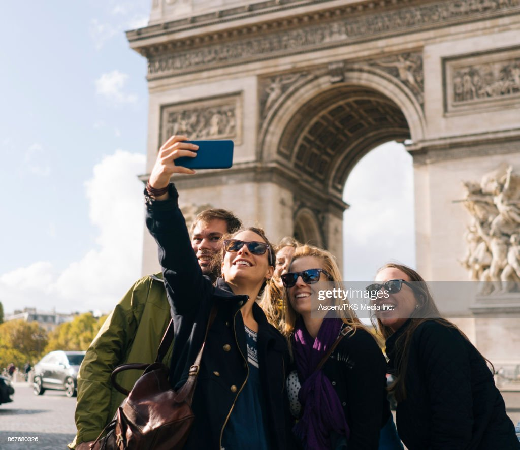 Group of friends pose for selfie in front of the Arc de Triomphe : Stock Photo