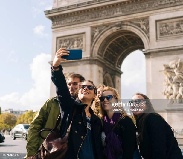 group of friends pose for selfie in front of the arc de triomphe - turismo urbano - fotografias e filmes do acervo