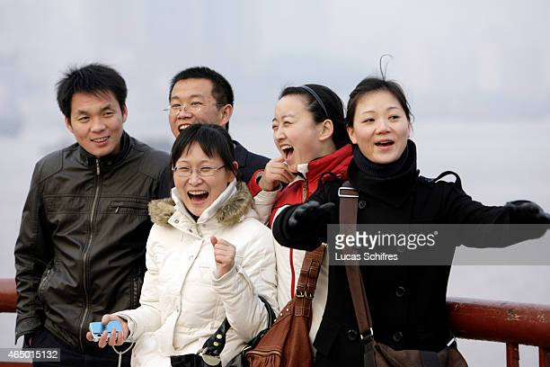 A group of friends poses for a photograph on the famous 'Bund' waterfront on January 8 2009 in Shanghai China