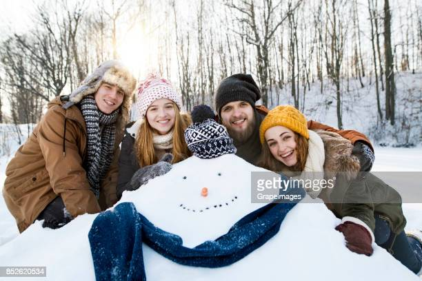 Group of friends posing with snowman.