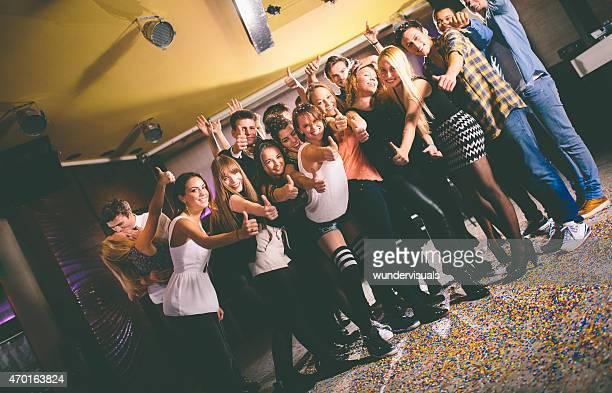 Grupo de amigos Posando com o polegar para cima no aparty
