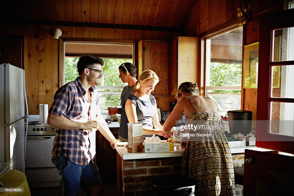 Group of friends preparing a meal in rustic cabin : Stock Photo