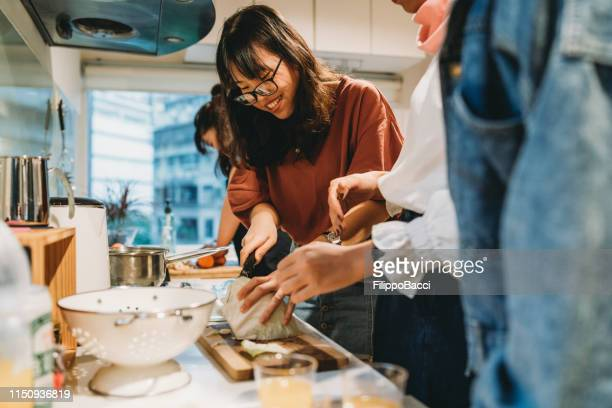 group of friends preparing dinner together in the kitchen - east asian ethnicity stock pictures, royalty-free photos & images
