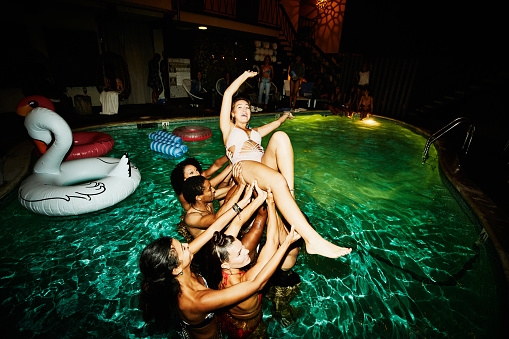 Group of friends preparing to throw woman in hotel pool during party - gettyimageskorea