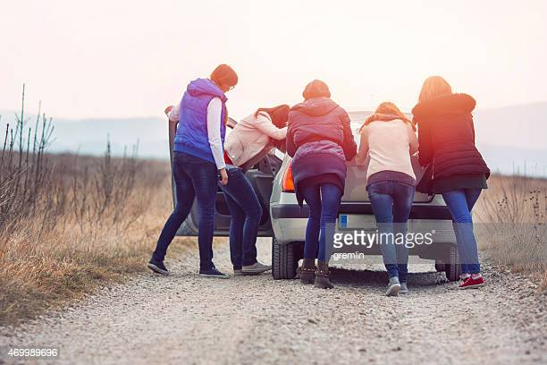 Group of friends pushing car on the rural road
