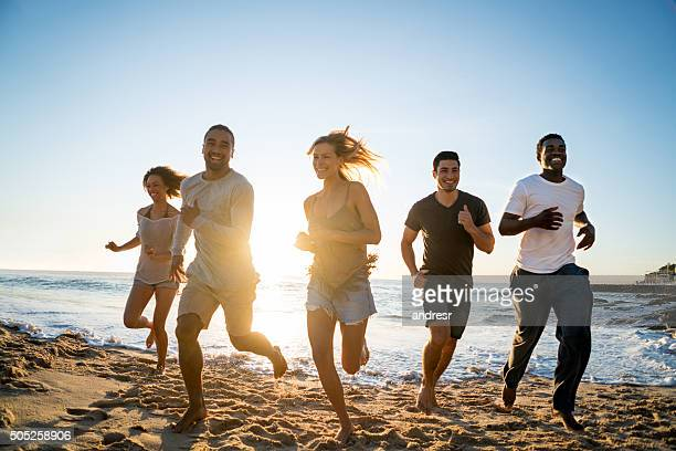 Group of friends racing at the beach