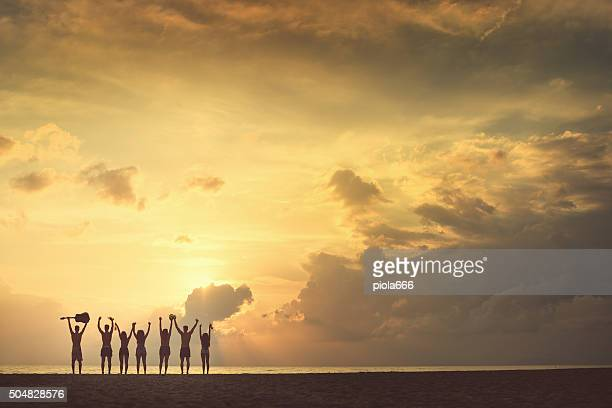 Group of friends raised arms to the sea