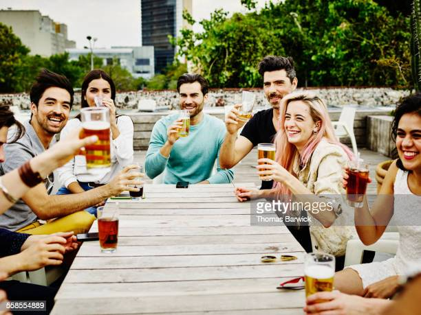 group of friends raising glasses to toast - mexican beer stock pictures, royalty-free photos & images