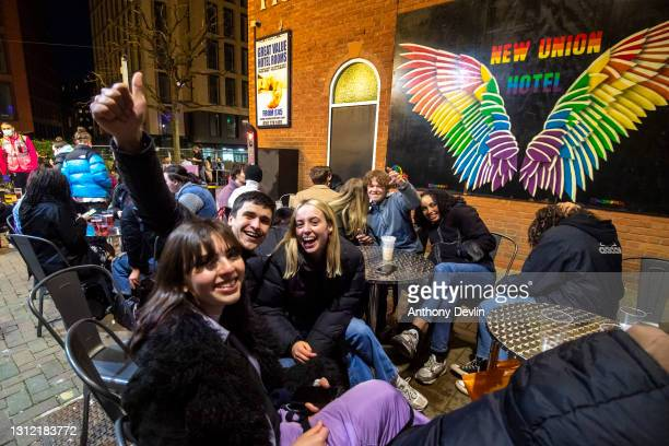 Group of friends react to the camera as patrons sit at tables outside bars on Canal Street on April 12, 2021 in Manchester, England. England has...