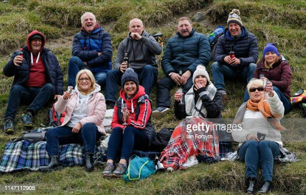 A group of friends react to the camera as they wait for the arrival of the peloton on the Cote de Park Rash ascent near the village of Kettlewell in...