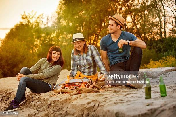 Group of friends relaxing by campfire, Osijek, Croatia