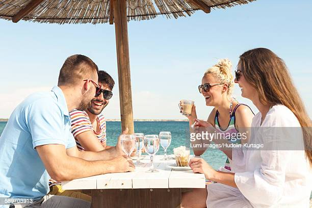 Group of friends relaxing in beach bar