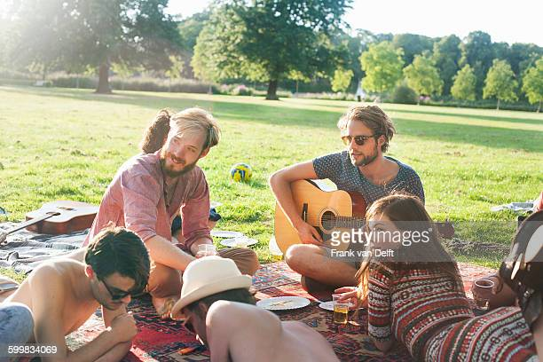 group of friends relaxing on rug at sunset park party - public park stock-fotos und bilder