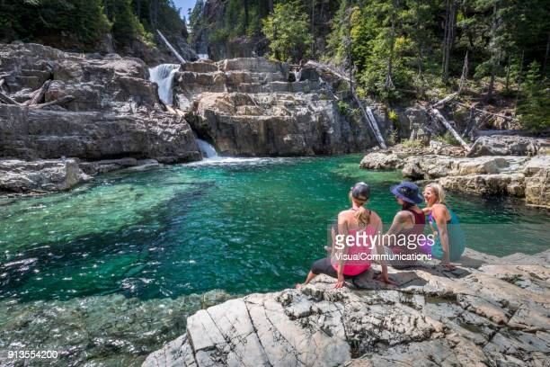 group of friends resting by waterfalls. - vancouver island stock pictures, royalty-free photos & images